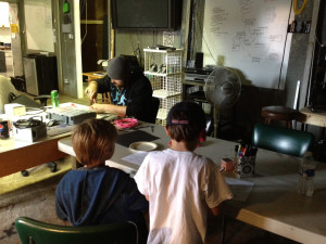 Duncan and Ollie work on paper masks as Dustin works on his Arduino LED project.